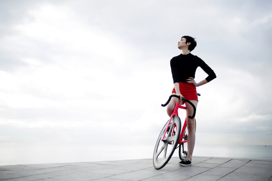 shutterstock-woman-posing-on-bicycle-in-front-of-clouds-051220
