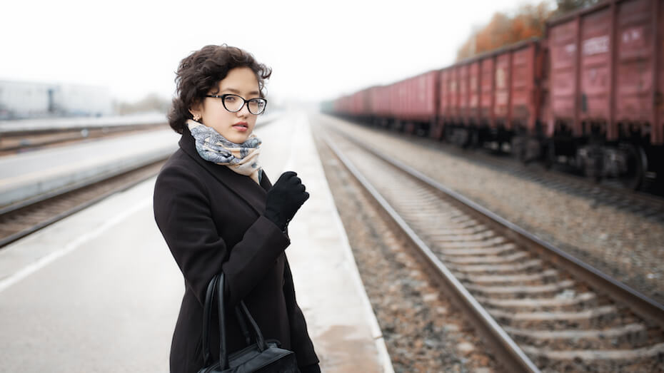 shutterstock-woman-standing-on-train-tracks-on-grey-cloudy-day-051220