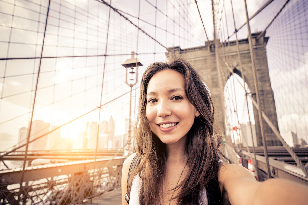 Shutterstock: Woman taking selfie on bridge