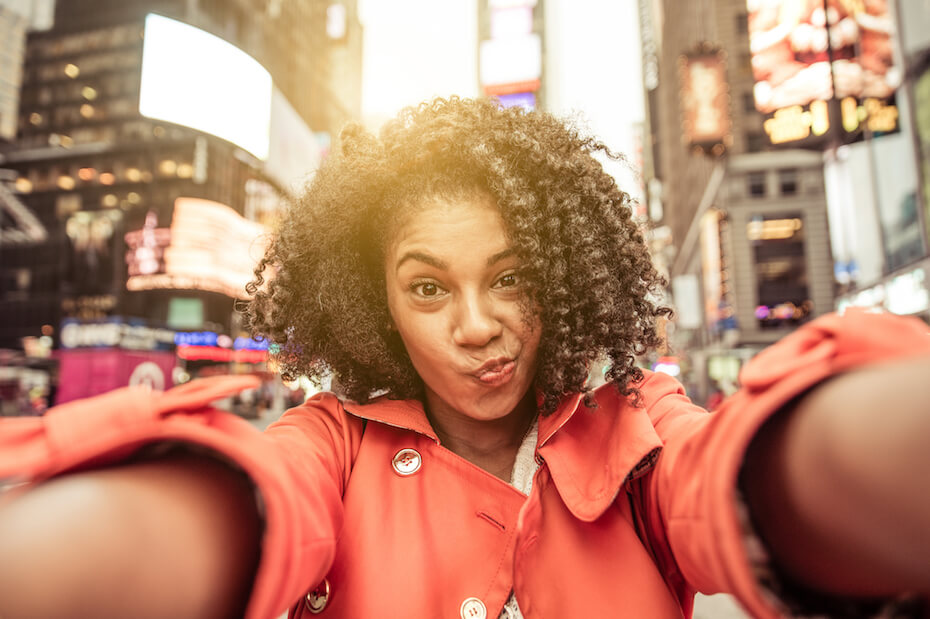Shutterstock: Woman taking selfie in the middle of city