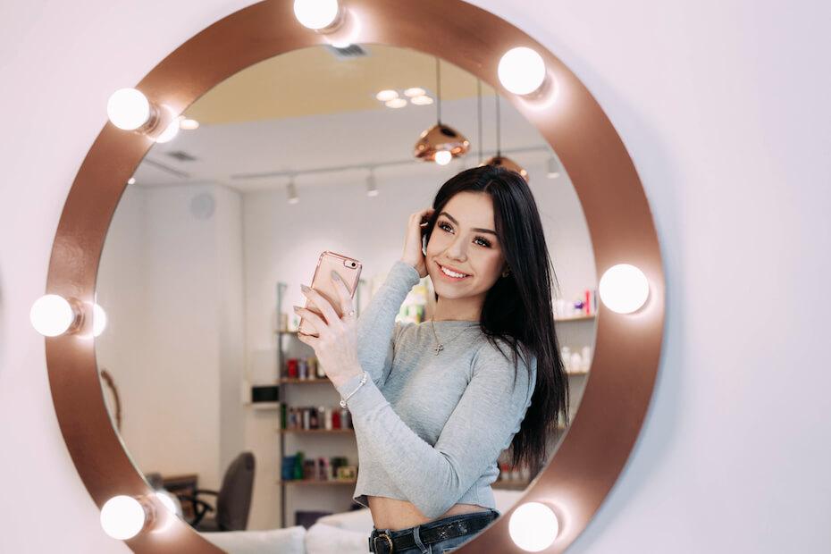 Shutterstock: Woman taking selfie in lighted mirror