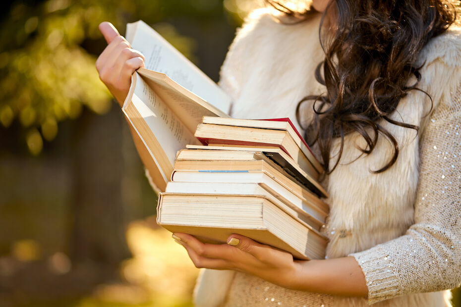 Shutterstock: woman with pile of books reading curious