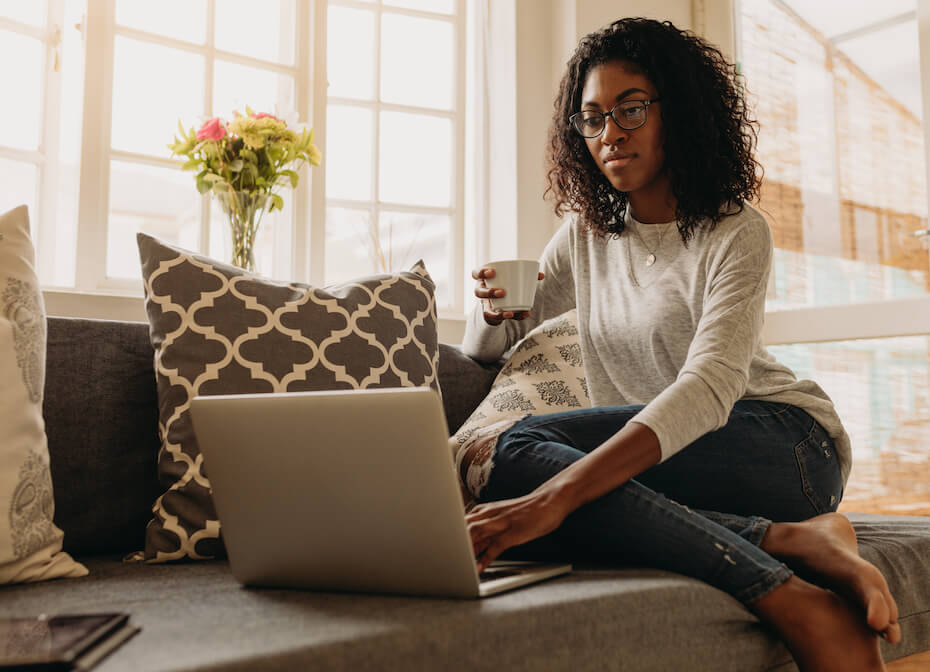 Shutterstock: Woman working from home on laptop computer on couch holding cup of tea coffee