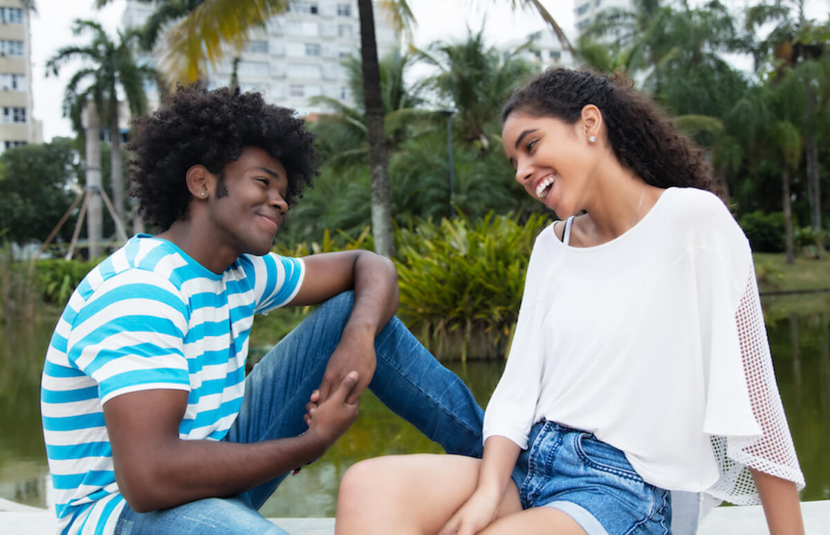 Shutterstock: Couple flirting talking and laughing at park
