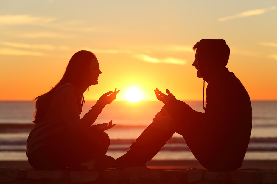 Shutterstock: Couple talking chatting debating at sunset