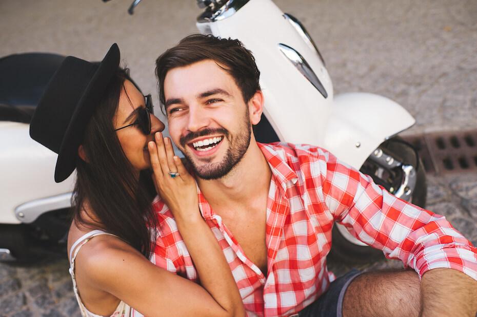 Shutterstock: Couple woman whispering in mans ear