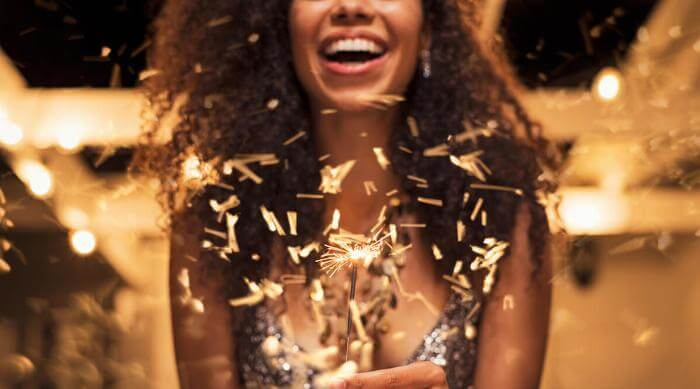 Shutterstock: Smiling woman holding up holiday sparkler