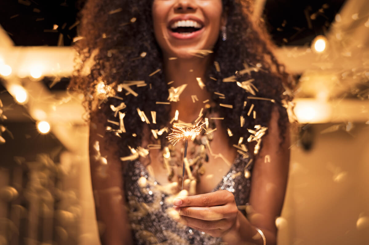 shutterstock-smiling-woman-with-holiday-sparkler