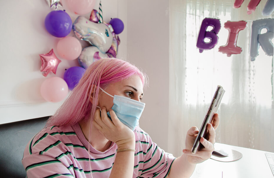 Shutterstock: Woman in face mask celebrating birthday alone at home in quarantine