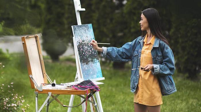 Shutterstock: Woman outside painting flower bush