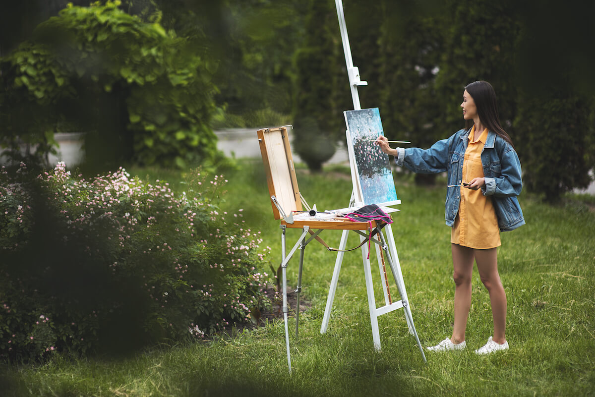 Shutterstock: Woman outside painting flower bush