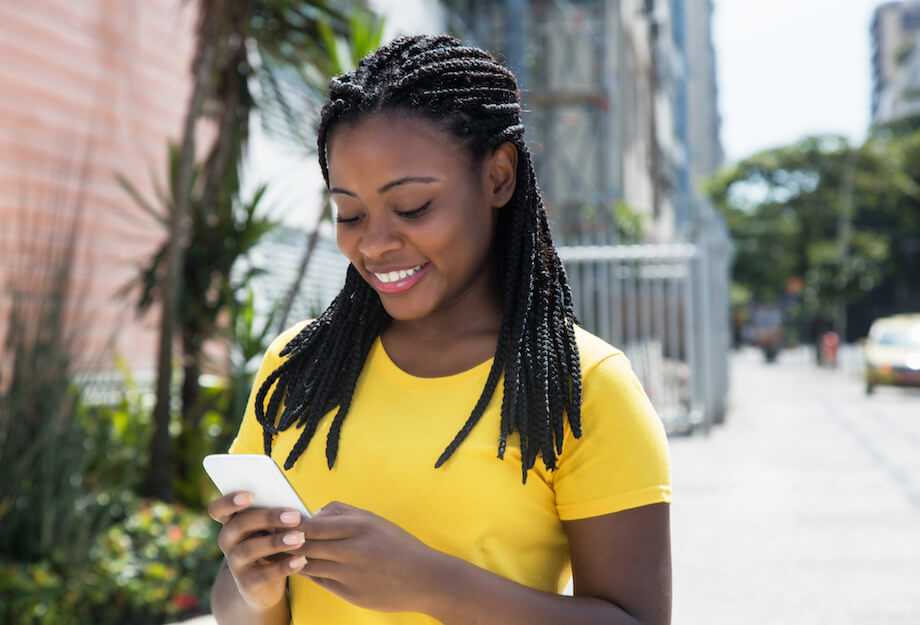 shutterstock-woman-texting-looking-at-phone-happy-outside-061220