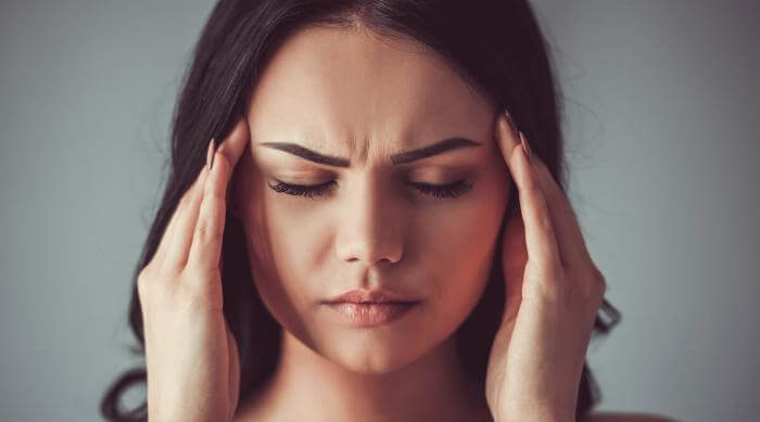 Shutterstock: Woman with headache touching temples