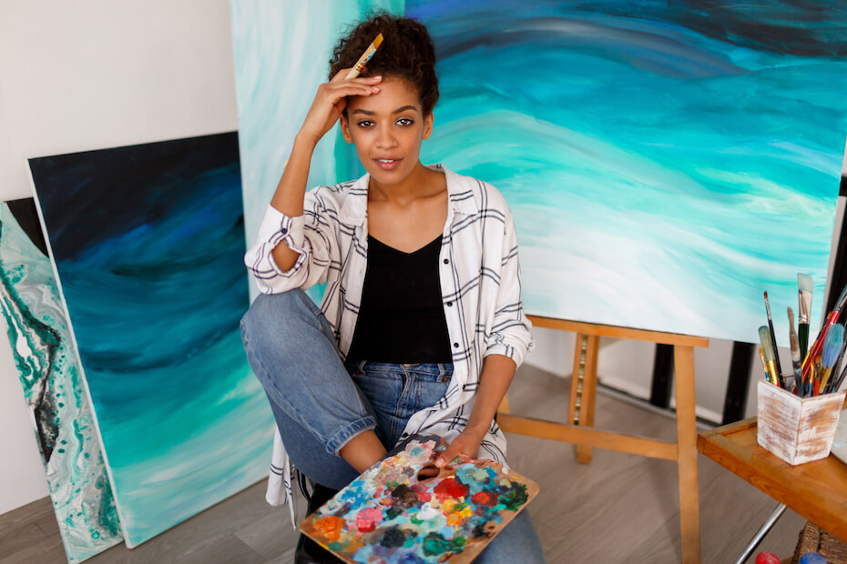 Shutterstock: Woman with palette in front of wave paintings