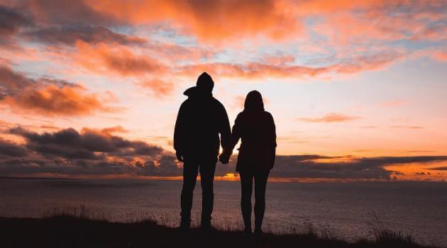 unsplash-alex-iby-couple-overlooking-cliff-beach-water-sunset-articleH-062620