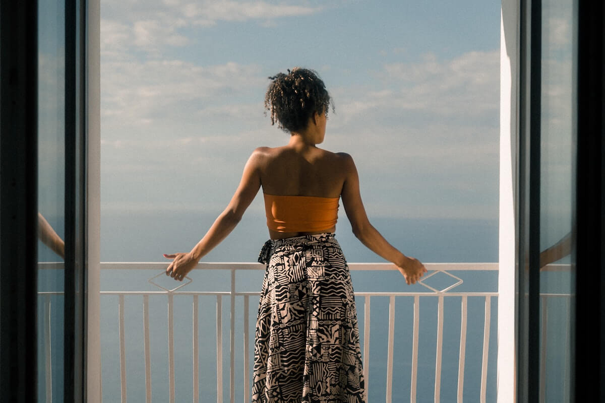 Unsplash: Woman looking over sea from balcony