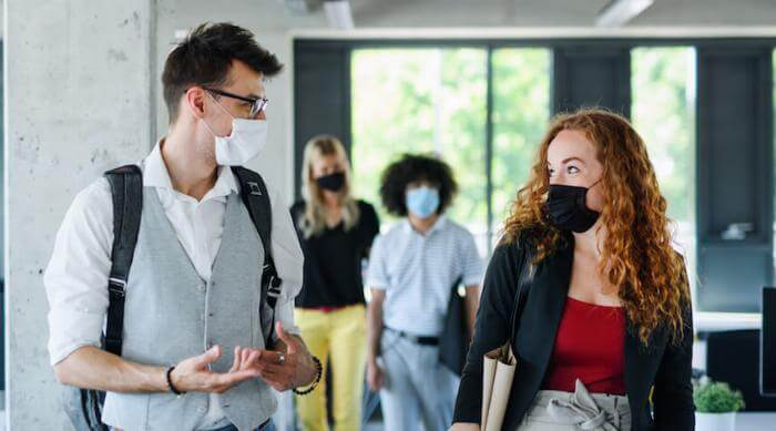Shutterstock: Man and woman talking and flirting wearing face masks