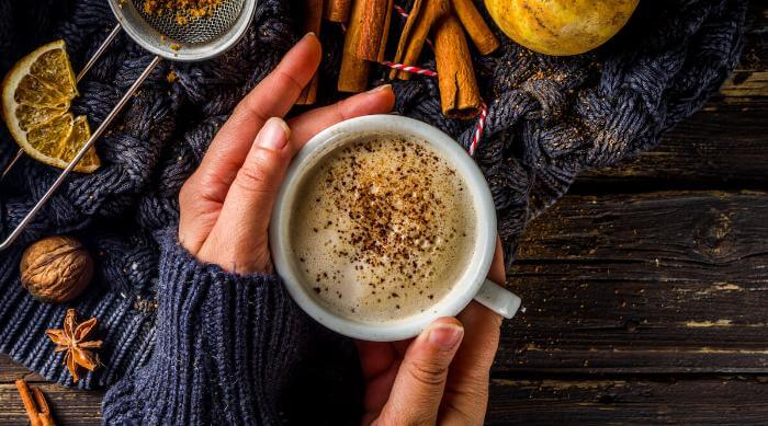 Shutterstock: Cozy photo of pumpkin spice latte in a mug being sipped by woman in sweater