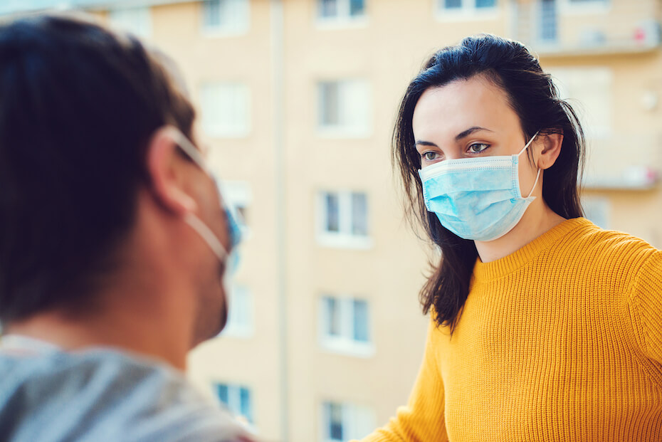 Shutterstock: Man and woman wearing masks and chatting