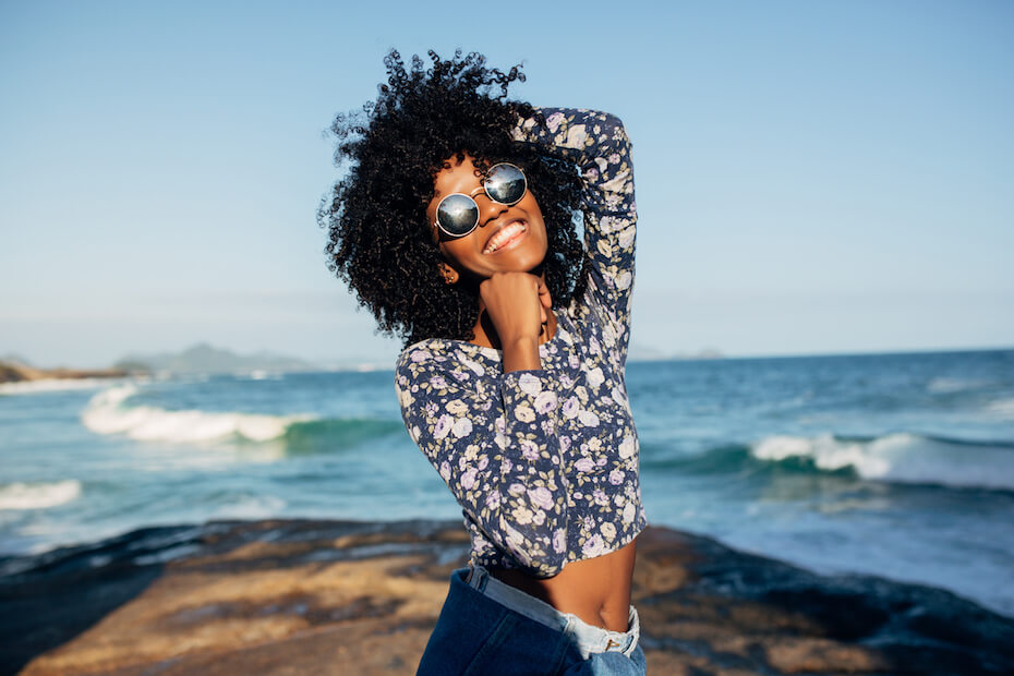 Shutterstock: Woman in sunglasses happy and smiling at the beach