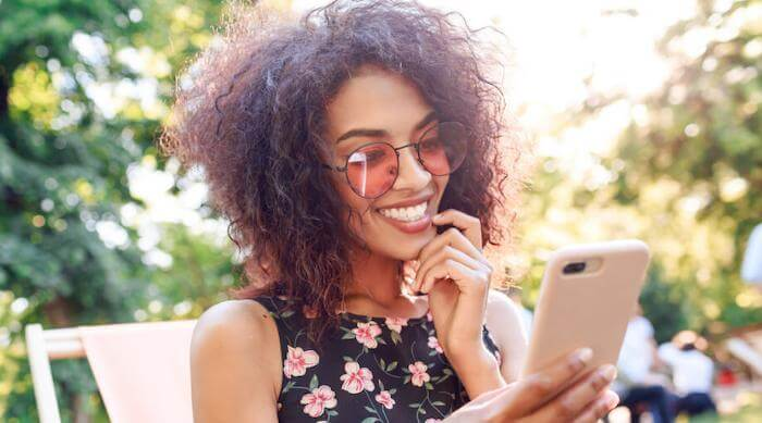 Shutterstock: Woman with rosy glasses on phone smiling