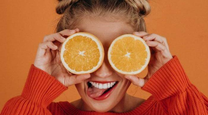 Unsplash: woman with two oranges, featured