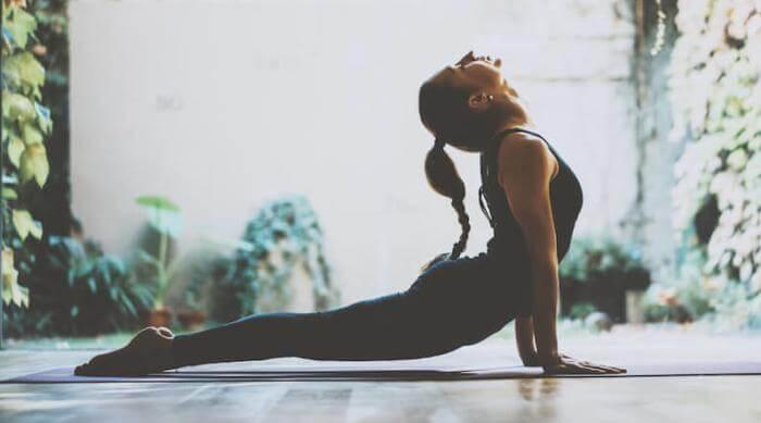 Shutterstock: woman performing upward dog pose