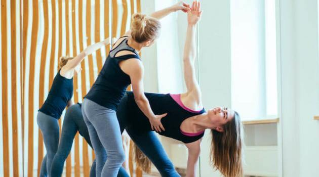 Shutterstock: yoga instructor helping student