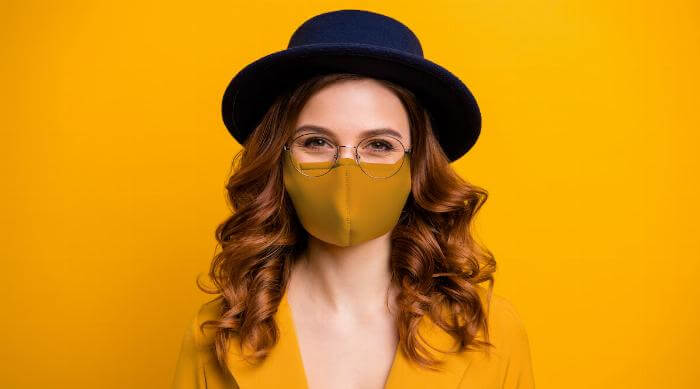 Shutterstock: Fashionable woman in yellow wearing glasses and face mask