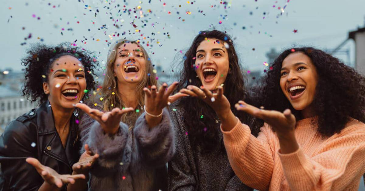 Shutterstock: four friends throwing sparkles into the air