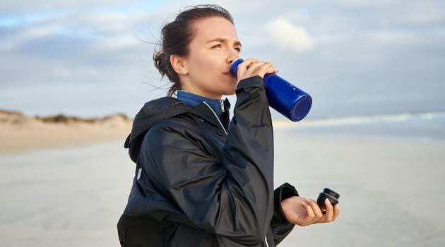 Shutterstock: woman drinking water on a beach