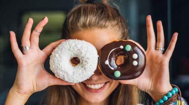 Shutterstock: woman holding two donuts in front of her face