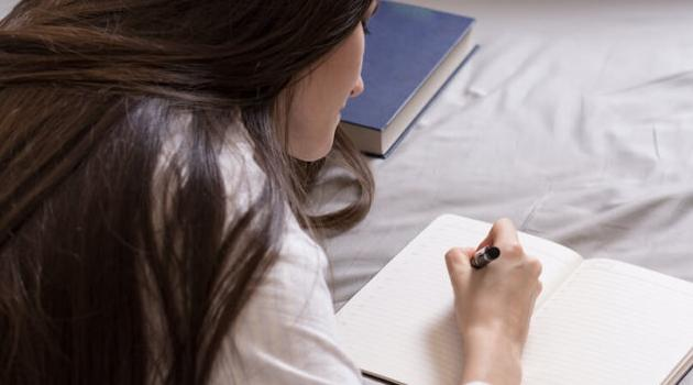 Shutterstock: woman journaling on her bed