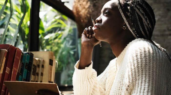 Shutterstock: woman journaling by window