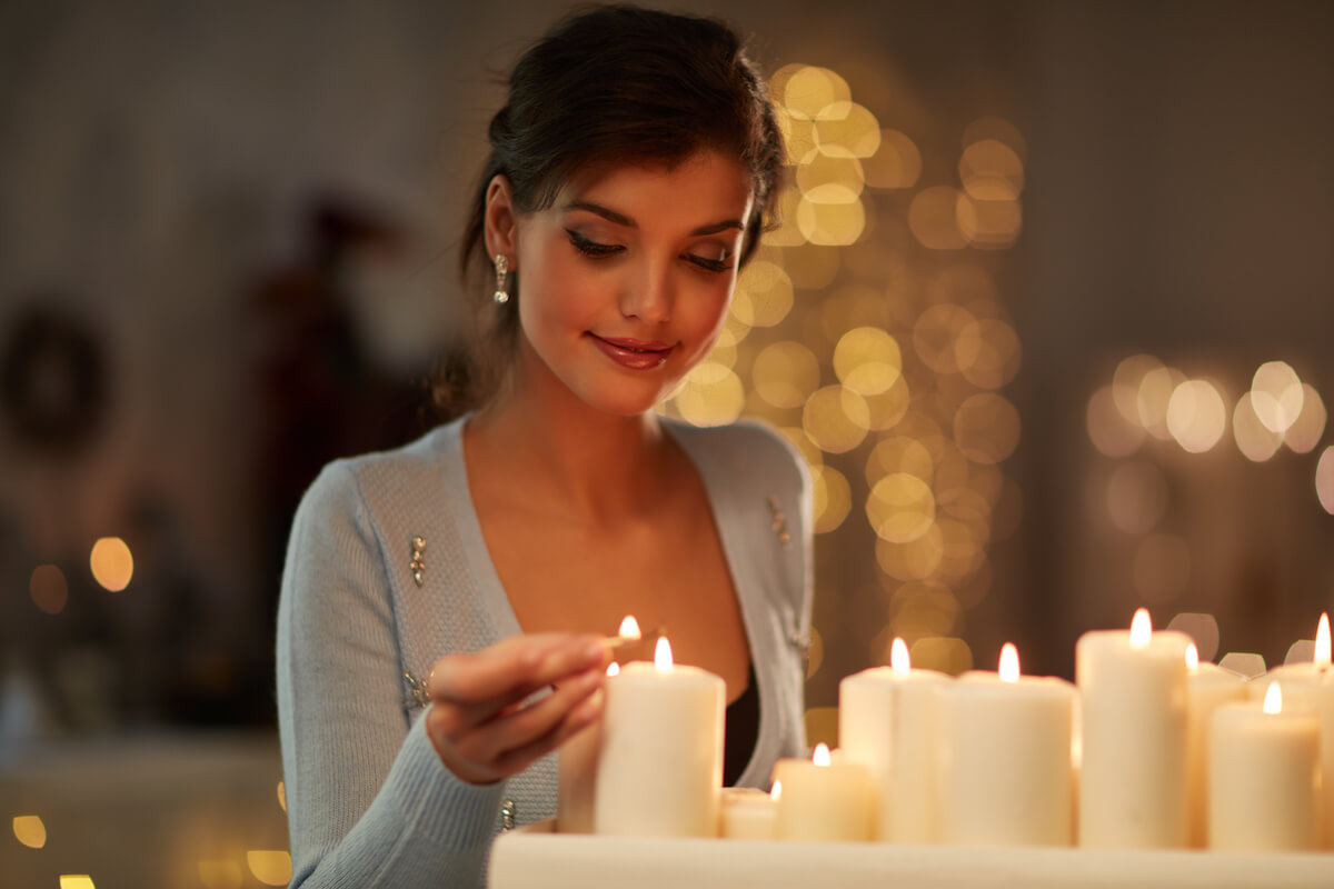 Shutterstock: Woman lighting white candles