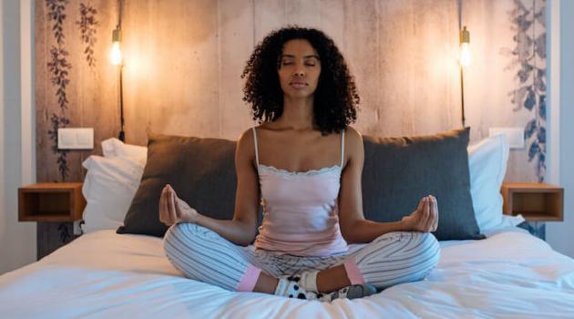 Shutterstock: woman meditating in bed
