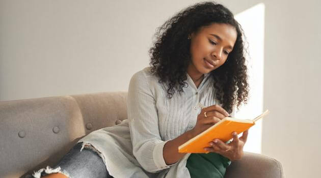 Shutterstock: woman journaling on couch