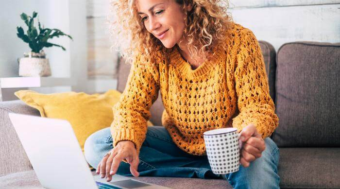 Shutterstock: Woman on touch working on laptop computer with coffee tea mug