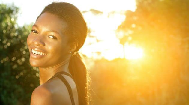 Shuttertstock: woman smiling in front of sunrise
