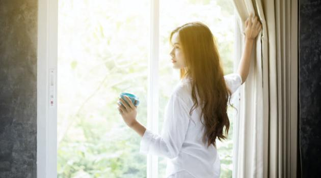 Shutterstock: woman opening curtains