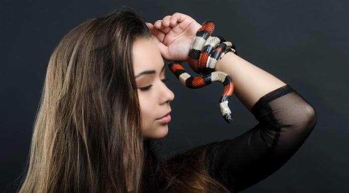 Shutterstock: Young woman holding up milk snake