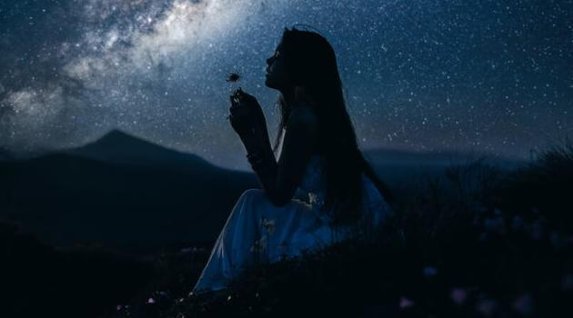 Shutterstock: girl looking at stars and holding flower