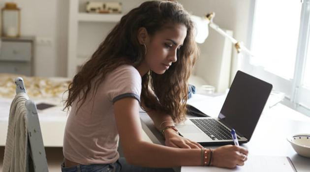 Shutterstock: girl taking notes next to computer