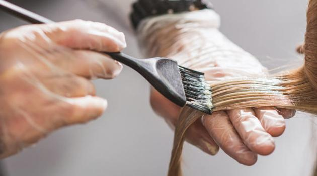 Shutterstock: hair stylist applying bleach to hair