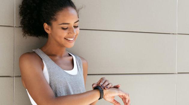 Shutterstock: woman checking fitness tracker