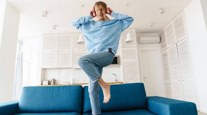 Shutterstock: Woman dancing at home on couch