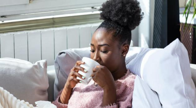 Shutterstock: woman drinking tea on couch
