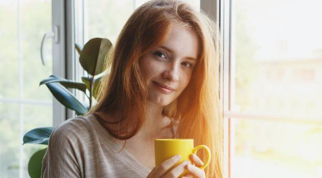 Shutterstock: woman drinking tea by window