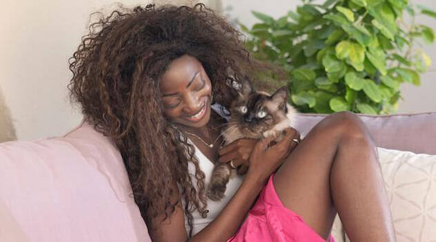 Shutterstock: woman holding a cat while sitting on the couch