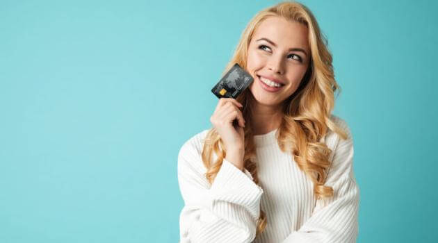 Shutterstock: woman holding credit card and wearing a white sweater in front of a light blue background